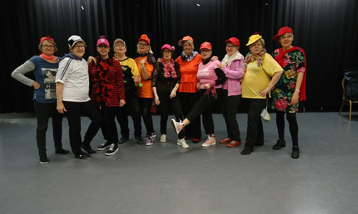 Ryhmä seniori-ikäisiä naisia poseeraa nuorekkaasti pukeutuneena.