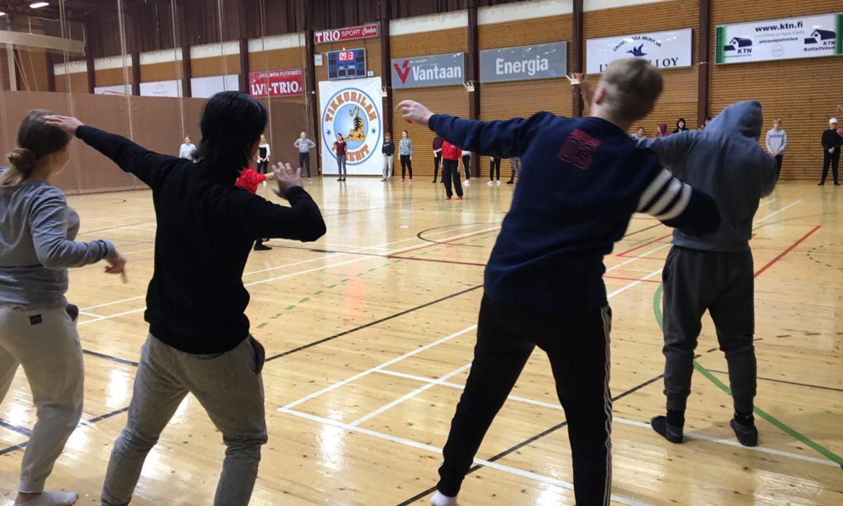 Joukko nuoria tanssii koulun liikuntasalissa ohjatussa työpajassa.