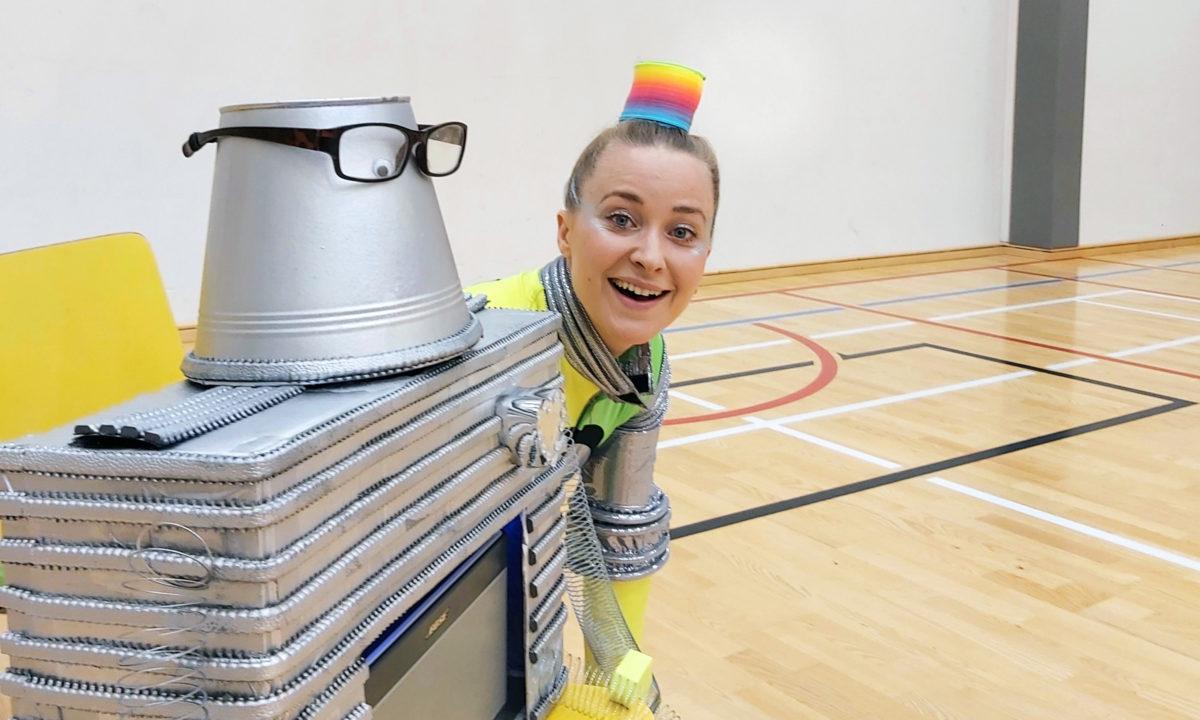 Kaksi robottia koulun liikuntasalissa. Tuolilla on metallinen robotti, jonka takana istuu hymyilevä robottihahmoinen tanssija.