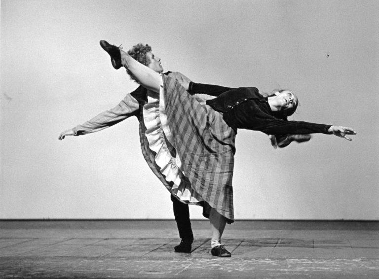 Kaksi tanssijaa, mies ja nainen. Mies pitää kiinni naisesta, joka ojentaa kättään ja vastakkaista jalkaansa.