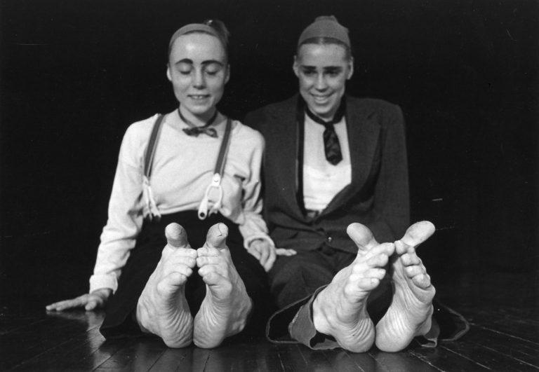Kaksi tanssijaa istuu ja ihmettelee hymyillen varpaitaan.